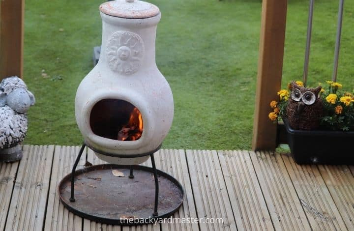 Chiminea on wooden deck with fire proof mat.