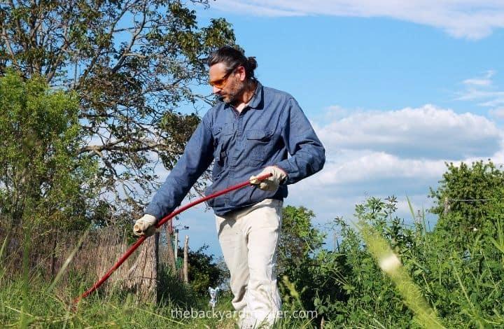 Man using scythe to cut grass.