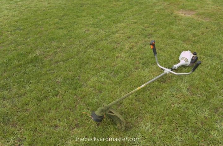 A weed wacker that was used to cut grass in a lawn.